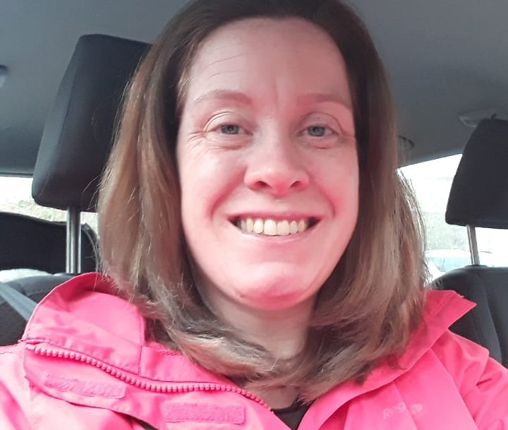 A woman dressed in a pink coat smiling at the camera